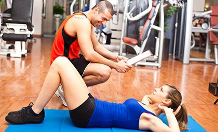 Trainer guiding client with fitness exercise